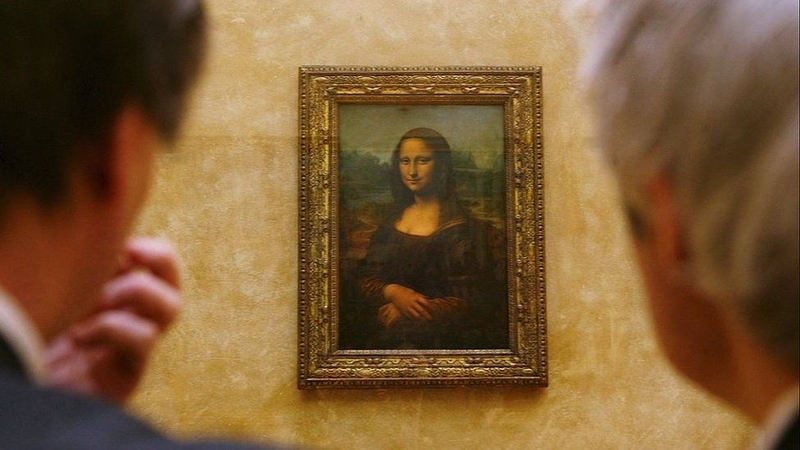 Two men in art gallery looking at mona lisa